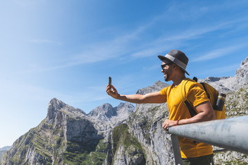 Latin Man Carrying a Yellow Backpack Hiking and Taking a Picture to the Mountain.