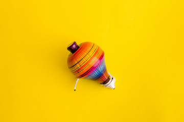 mexican toys, trompo from Wooden in Mexico on yellow background