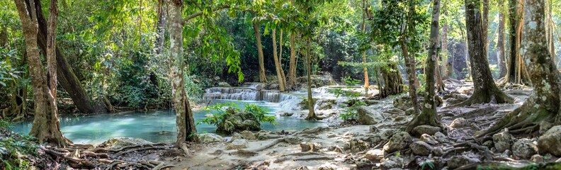 Panorama of bare tree roots and a series of beautiful short waterfalls in the dense forest of Erawan National park in Thailand