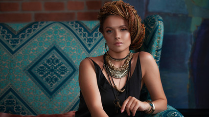 Southern spices. Luxurious young woman with afro-hairs, an intricate hairstyle, with large jewels in ethnic style.