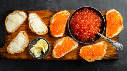 Close-up red caviar in bowl and Sandwiches on wooden cutting board on black background. Top view. Flat lay