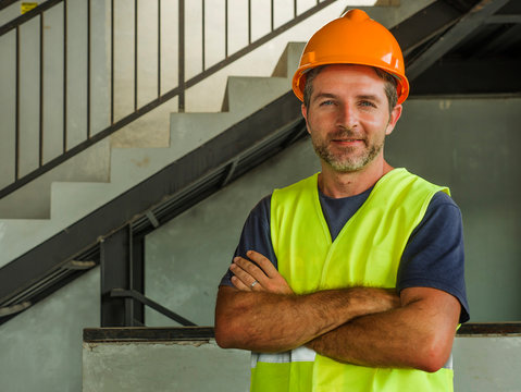 Corporate portrait of young attractive and happy builder man or constructor posing confident smiling wearing building helmet and vest in blue collar job lifestyle