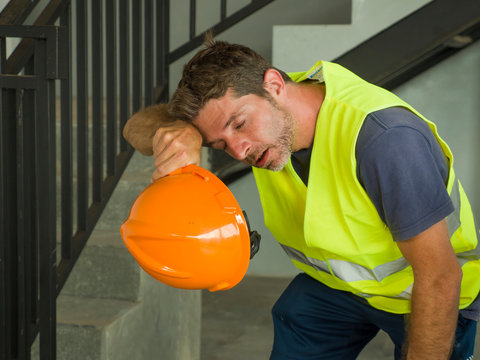 Portrait of attractive and exhausted construction worker in helmet and vest at building site taking a breath during a hard working day all sweaty and tired