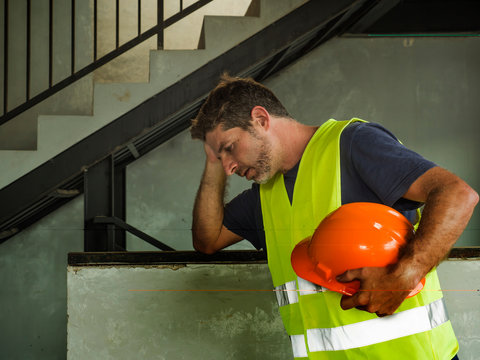 . Attractive stressed and frustrated construction worker man in vest and builder helmet looking tired and worried suffering problem in blue collar job lifestyle concept