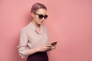 A girl with short pink hair in a blouse, skirt and sunglasses looks at a smartphone while standing on a pink background.