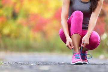 Autumn running shoes girl tying laces ready to run in forest foliage background. Sport runner woman training cardio in outdoor fall nature in pink activewear leggings and footwear.