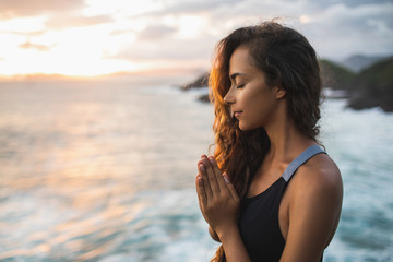Young woman praying and meditating alone at sunset with beautiful ocean and mountain view. Self-analysis and soul-searching. Spiritual and emotional concept Fototapete