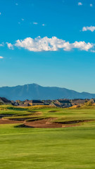Vertical frame Picturesque view of a golf course with residences and mountain in the background