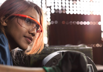Diverse female mechanical engineer operating heavy industrial machinery - Dark skin Asian woman working in engineering workshop wearing safety glasses - diversity, factory and workplace concept