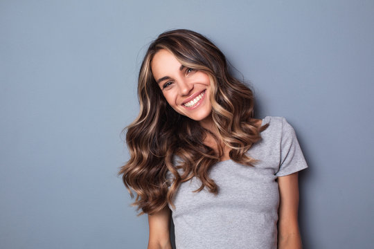 Smiling young woman on grey wall background.