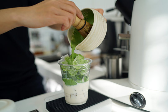 Iced matcha latte - A glass of green tea with milk on the table, Summer refreshment drinks.