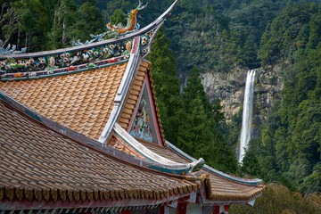 Curved roofs of colorful Chinese temple and Nachi waterfalls on the background. Wakayama. Japan