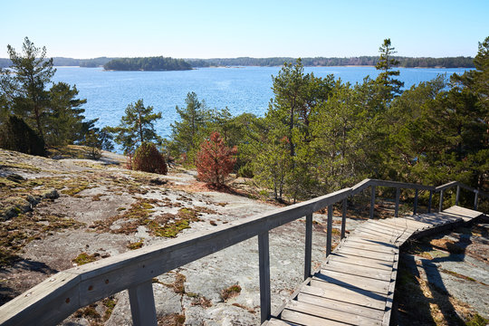 Wooden stairs leading down from the rocks towards the sea. sunny spring day at Finnish archipelago in the Kemiö Island, Finland.