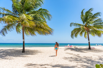 Beach tropical vacation in Barbados Caribbean travel holiday, Dover beach woman walkingin the sun in swimsuit happy on beach, Summer destination. .