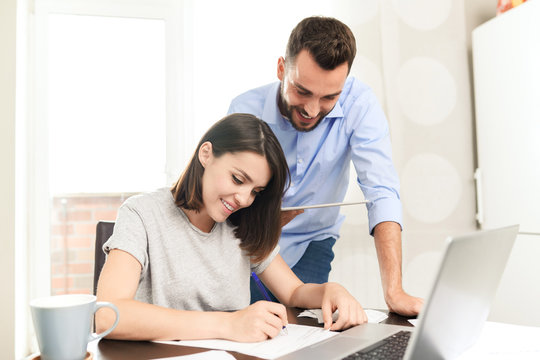 Content confident young man using tablet app while assisting girlfriend