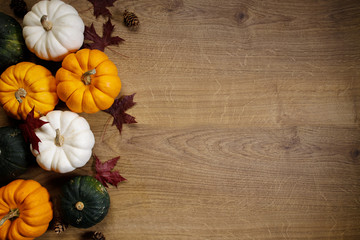 Pumpkins and rad maple leaves on wooden background, top view