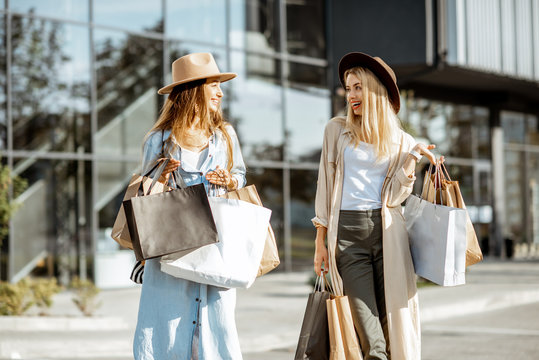 Two happy girlfriends walking with shopping bags in front of the shopping mall, feeling satisfied with new purchases