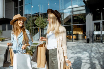 Two happy girlfriends walking with shopping bags in front of the shopping mall, feeling satisfied with new purchases Wall mural