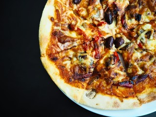 A close up shot of a freshly cooked delicious supreme pizza on a white plate on a black table at a restaurant.