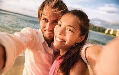 Wall Mural - Happy smiling biracial couple taking selfie photo with camera phone. Caucasian man holding smartphone on beach vacation holiday sunset.