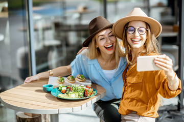 Canvas Prints Restaurant Two female best friends making selfie photo while sitting together on a restaurant terrace and eating healthy food