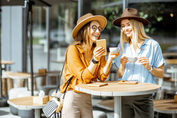 Fototapeta Two female best friends spending time together on the cafe terrace, feeling happy standing with coffee and phone during a summer day obraz