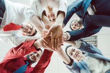 Team of diverse business people stacking their hands together