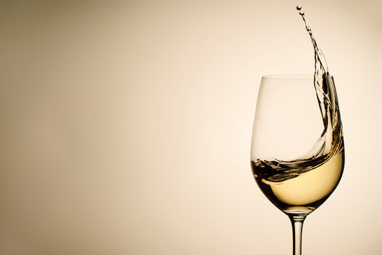 Suspended drops and splash of white wine in glass