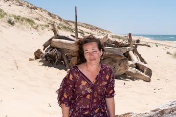 Fototapeta woman on sand beach driftwood and dunes background obraz