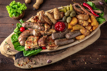 Fotobehang Grill / Barbecue Assorted meat. A large beautiful wooden plateau with juicy pieces of pork, beef, chicken, meat. Grilled sausages, bones, ribs, fillets, barbecue with appetizer of pickles and potatoes.