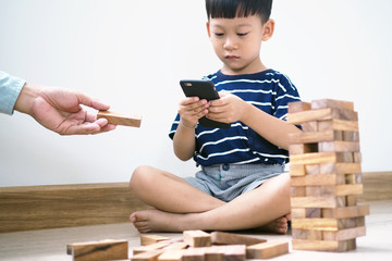 Asian children in the age of social networks that focus on phones or tablets. Do not care about the surrounding environment and have eye problems.