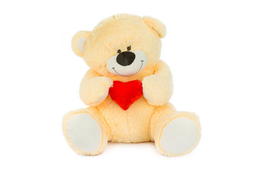 Image of golden toy teddy bear holding red heart and sitting at isolated white background.