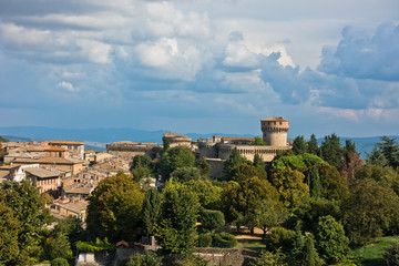 Cityscape of Volterra over the roofs with surrounding landscape, Medici fortress in background, Tuscany, Italy