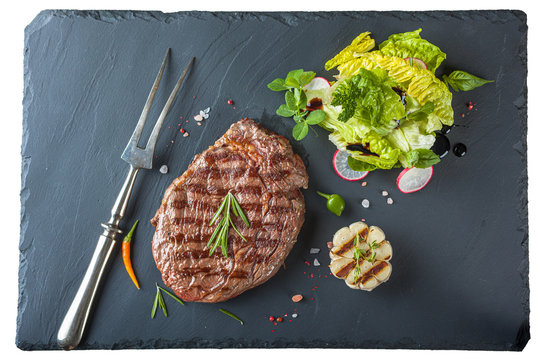 The ribeye steak with sprig of rosemary anh salad on a black stone slab