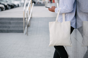Young man holding white textile eco bag against urban city background. . Ecology or environment...