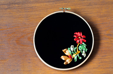 Hand embroidery with red, gold and green satin ribbons of flowers pattern on black velvet. Hobby, craft and needlework (embroidery was made by the author of the photo). Place for text, flat lay