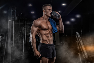 A young handsome man with big muscles, holds a shaker with protein, rest after cross-training