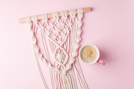 Creative flat lay concept, coffee cup and macrame panel on pastel pink background and copy space, minimal style, saint valentine romance trendy composition
