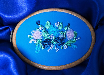 Needlework. Close up view for the hand embroidery with satin and nylon ribbons of flower ornament with delicate roses in frame on blue fabric (the embroidery made the author of photo)