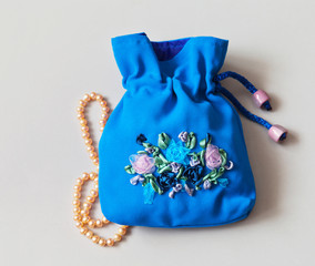Handmade blue bag for jewelry with embroidery with satin and nylon ribbons on a light background. Holiday Gift (the embroidery made the author of photo)