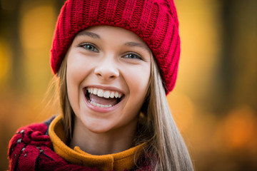 autumn portrait of a girl in a red knitted hat
