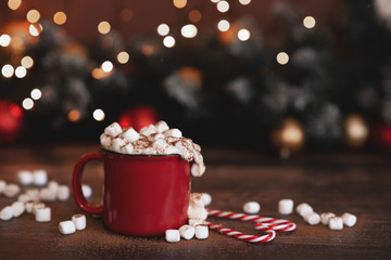 Winter whipped cream hot coffee in a red mug with star shaped cookies and warm scarf - rural still...