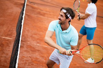 Picture of handsome young man on tennis court. Man playing tennis. Man throwing tennis ball. Beautiful forest area as background