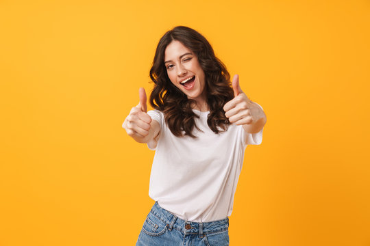 Image of beautiful brunette woman wearing casual clothes winking and showing thumbs up at camera