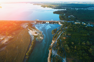 Aerial view of Dam at reservoir with flowing water at sunset, hydroelectricity power station, drone photo
