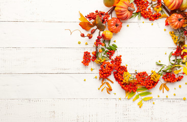 Autumn concept with pumpkins, flowers, autumn leaves and  rowan berries on a white rustic background. Festive autumn decor, flat lay with copy space.