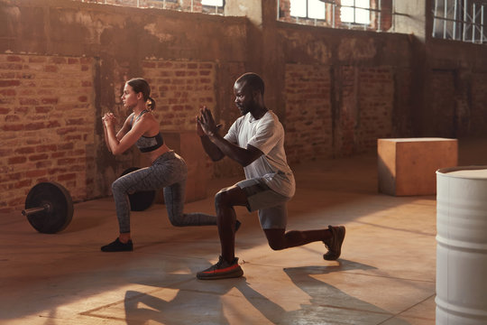 Sport couple doing leg lunge exercise workout at gym