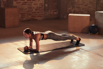 Fitness woman doing plank exercise workout in gym indoors