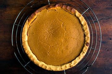 Overhead view of pumpkin pie on cooling rack
