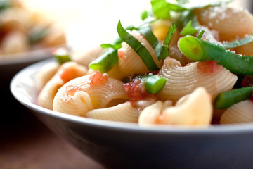 Close up of pasta with salsa crudo and green beans served in bowl